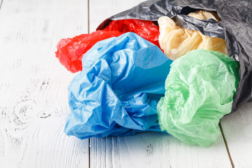 Image of multicolored plastic bags spilling out of a black plastic bag on a white wooden background.