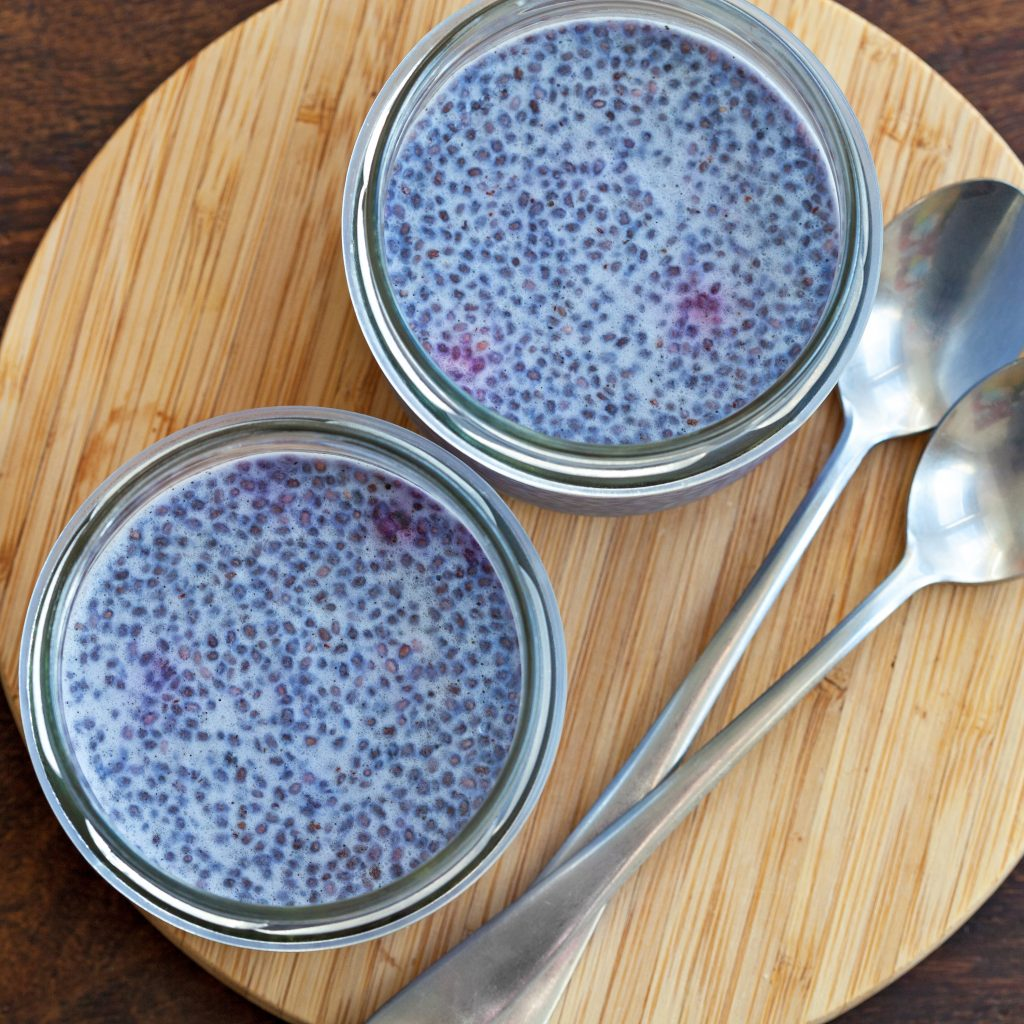 Two jars of lavender chia seed pudding with two spoons all on top of a wooden cutting board